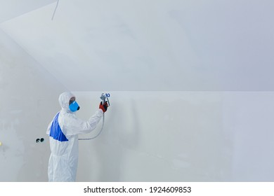 Airless spray paint. The worker paints the wall with an airless spray in white, an experienced worker sprays the paint on the surface with a mechanical air tool