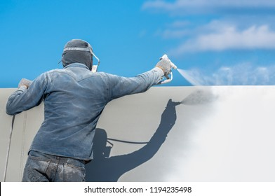 Airless Spray Painting, Worker painting on steel wall surface by airless sapray gun for protection rust and corrosion.