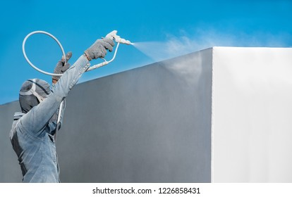 Airless Spray Painting, Worker painting on steel wall surface by airless sapray gun for protection and corrosion.