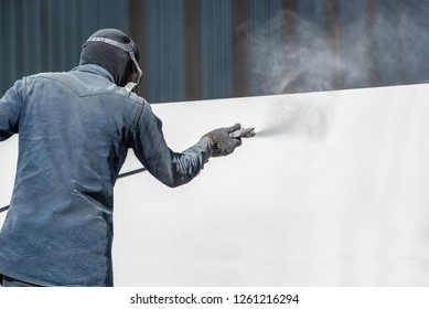 Airless Spray Painting, Worker painting on steel wall surface by airless spray gun for protection rust and corrosion.
