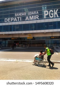 Airline crew escort an old man on wheelchair after landed in Depati Amir International airport, in Pangkal Pinang city, Central Bangka province, Indonesia - August 18th 2009.
