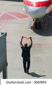 Airline ground crew directing an aircraft to the airport gate