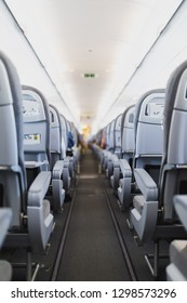 airline passenger seats and aisle in airplane cabin