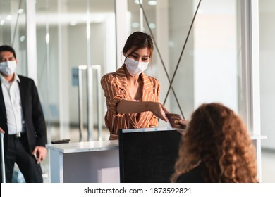 Airline passenger wear face mask at  check in counter in airport with staff wear face shield. New normal concept of travel after Covid-19 pandemic