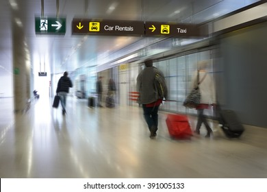 Airline Passengers in an Airport with Car Rental Sign and Taxi Sign