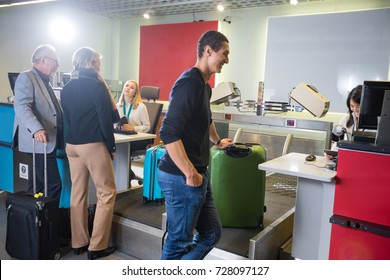 Airline Passengers Weighting Their Baggage At Airport