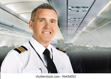 Airline pilot wearing uniform with epaulettes on board of passenger aircraft.