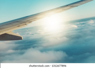Airline wing fly in cloudy blue sunny sky. Tourist passenger experience full service of long haul flight in holiday, vacation travel, business trip. Innovation technology save eco system reduce CO2