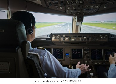 Airliner captain in cockpit are controlling the airplane to take off on the runway. He is moving forward the throttle in TOGA position. Modern airplane and aviation concept.