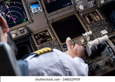 Airliner captain controlling airplane in cockpit. He pulling spreed brake lever to slow down the aeroplane speed by right hand. Seen behind pilot seat. Modern aviation concept.