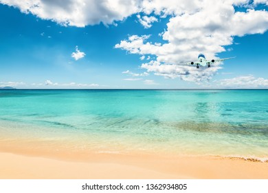 Airliner in the distance above the beautiful Caribbean ocean, will land at the beach of Sint Maarten. Travel backgrounds.