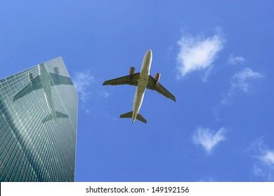 An Airliner in Flight with Reflection in Skyscraper Glass