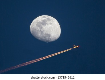 An airliner at high altitude passes by a waxing gibbous moon at sunset.