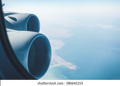 Airliner jet engines and coastal landscape, airplane in flight