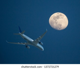 An airliner at low altitude passes by a waxing gibbous moon at sunset.