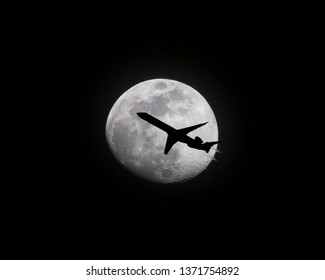 An airliner at low altitude is silhouetted as it passes in front of a full moon at night.