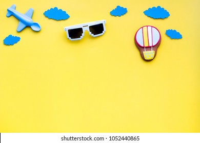 Airplan, air balloon toys and paper clouds for family traveling with child on yellow background top view mock-up