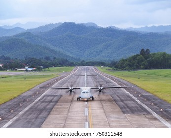 An Airplane / Aeroplane Was Taxiing, Landing, or Taking off on Runway in The Airport Surrounded by Mountains or Hills.