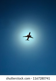 airplane against sun and blue sky