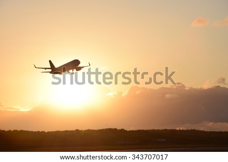 Airplane in the air and sunset in background