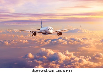Airplane airliner flies over beautiful evening clouds, in the sky at sunset