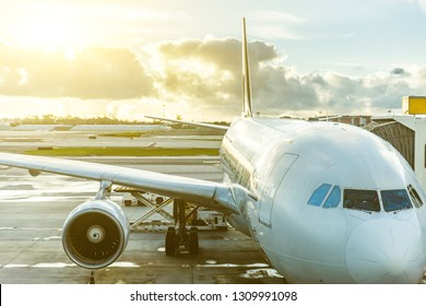 Airplane at airport close up view at sunset. Long haul flight big aircraft ready to leave from gate. Dramatic sky with clouds at sunset. Travel and transportation concepts