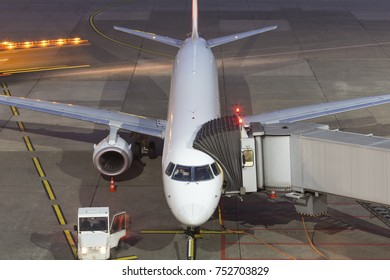 airplane at an airport gate at night