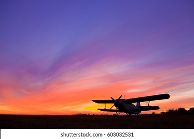Airplane AN-2 at standing position. Sunset scene.