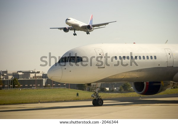 Airplane approaches as another waits to takeoff