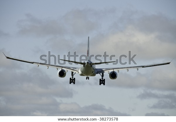 Airplane from the back end. It is ready to land with all wheels down.