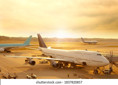 Airplane being prepared for departure at the tarmac of an airport at sunrise.
