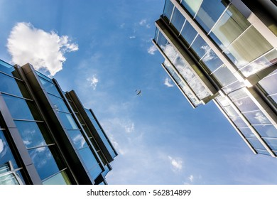 an airplane between two glass buildings