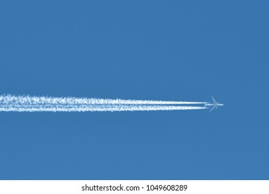 Airplane In Blue Clear Sky With Plane Trails