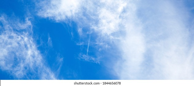 Airplane in the blue sky with clouds from below, high flying passenger plane with condensation trail. jet plane flying overhead diagonally in sky with sunlight. Bottom view