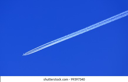 Airplane in Blue Sky with Condensation (Vapor) Trail