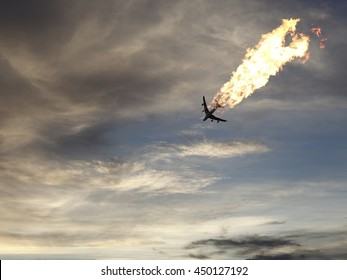 An airplane burning in midair over an evening sky.