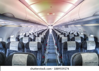 Airplane cabin and aisle with empty comfortable seats in economy class inside of plane