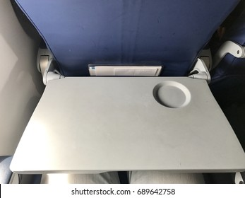 Airplane cabin is all white. All its decorations are necessary stuffs and safety. The grey Tray table for passenger in plane.
