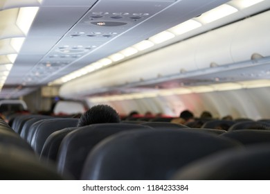 Airplane cabin selective focus background shows airplane seats with passenger inside the plane with travel concept