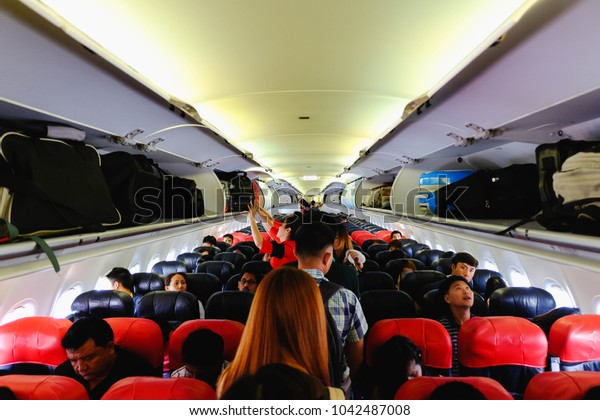 Airplane chiang rai, Thailand- december 11, 2017 : Interior of Air asia airplane with passengers sitting on seats and stewardess walking the aisle in background
