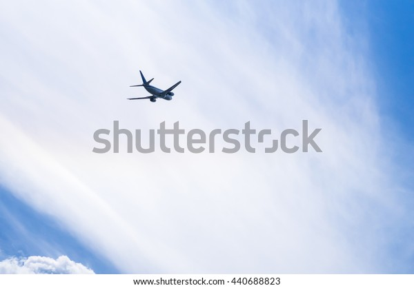 Airplane in Clouds. Airplane after taking-off on the background of cloudscape. Copy Space and Background Photo.
