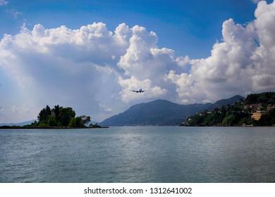 Airplane in the cloudy sky off the coast of Corfu island in Greece