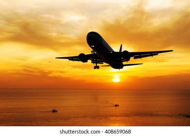 Airplane come down to the land on blurred sea sunset in twilight