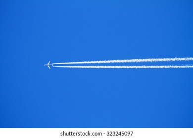 Airplane with condensation trails on blue sky.