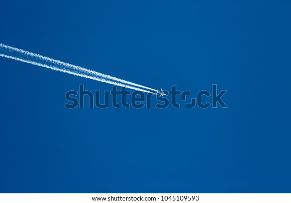 Airplane with Contail in blue clearly sky.An artificial cloud made by the exhaust of jet aircraft or wingtip vortices that precipitate a stream of tiny ice crystals in moist, frigid upper air.