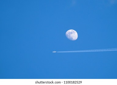 airplane with contrail on sky and moon