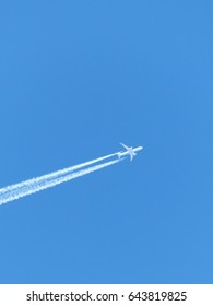 Airplane with contrails in a clear blue sky, Cruising altitude