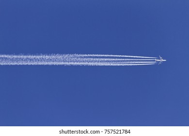 Airplane and contrails on clear blue sky.