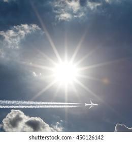 An airplane creating jet stream trail across a bright shining sun.