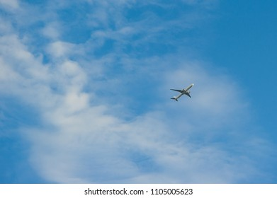 Airplane in the deep cloudy sky at summer